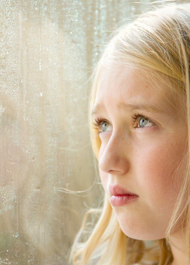 Primer de un adolescente mirando hacia fuera una ventana imágenes de archivo libres de regalías