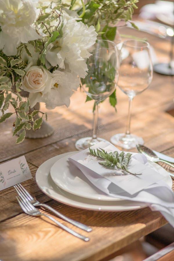 Primer de un ajuste de la tabla con las flores del rústico-estilo para las huéspedes en una boda o una fiesta de cumpleaños imagen de archivo libre de regalías