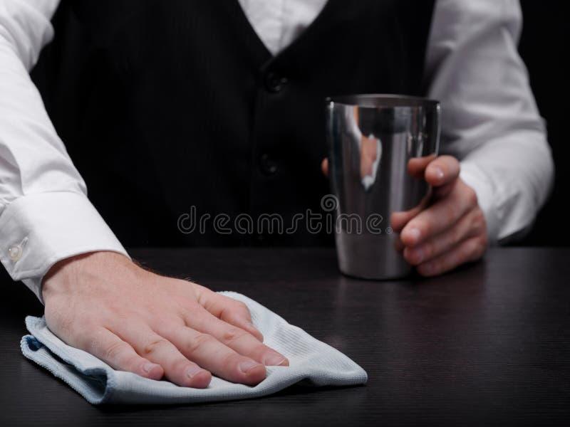 Primer de un camarero que limpia un contador de la barra Barkeeper con una coctelera y un pañuelo blanco en un fondo negro imagen de archivo