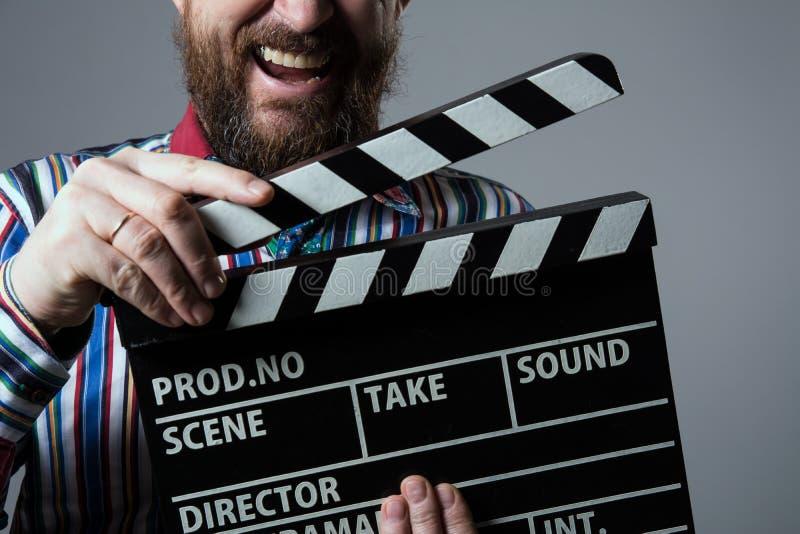 Primer de un cine sonriente del clapperboard del hombre fotos de archivo