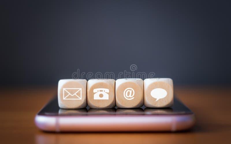 Primer de un dado de madera de los iconos del teléfono, del correo electrónico, de la charla y del poste que arregla en fila en e stock de ilustración