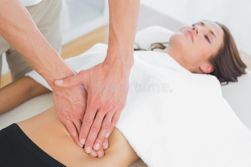 Primer de un fisioterapeuta que da masajes al cuerpo de la mujer imágenes de archivo libres de regalías