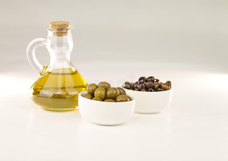 Primer de un frasco con aceite de oliva virginal adicional y dos pequeñas tazas con diversas variedades de aceitunas en el fondo  imagen de archivo