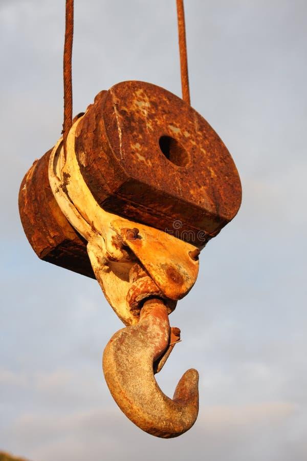 Primer de un gancho oxidado colgante de una grúa grande con el fondo azul natural foto de archivo