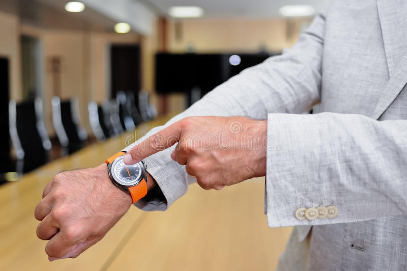 Primer de un hombre de negocios que muestra al suyo el reloj imagen de archivo