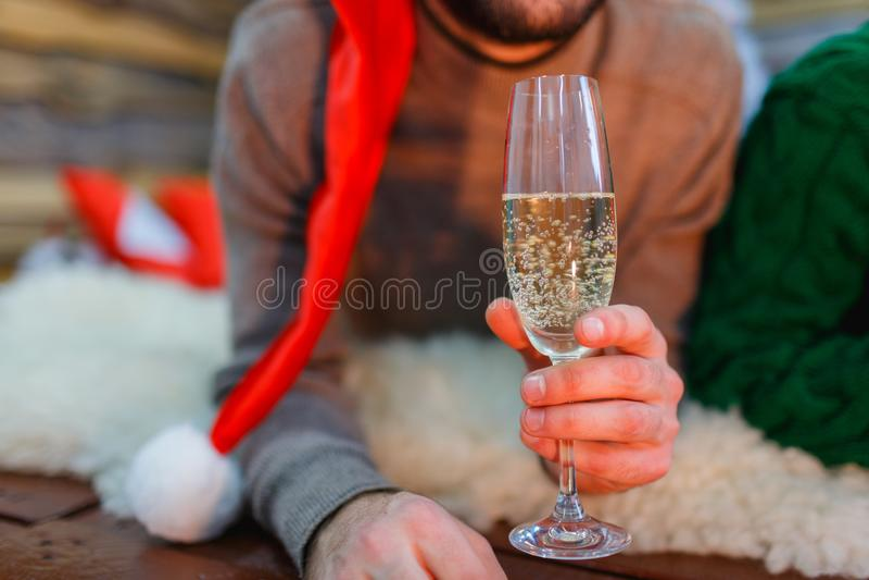 Primer de un hombre en un sombrero de santa que sostiene un vidrio de champán en sus manos foto de archivo