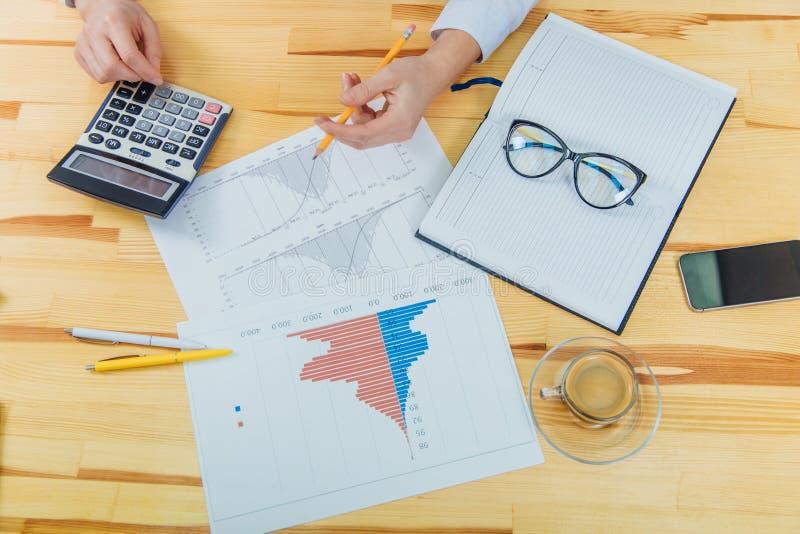 Primer de un hombre de negocios femenino que trabaja en una carta elegante del teléfono y de negocio Cálculo de estadísticas usan imagen de archivo libre de regalías