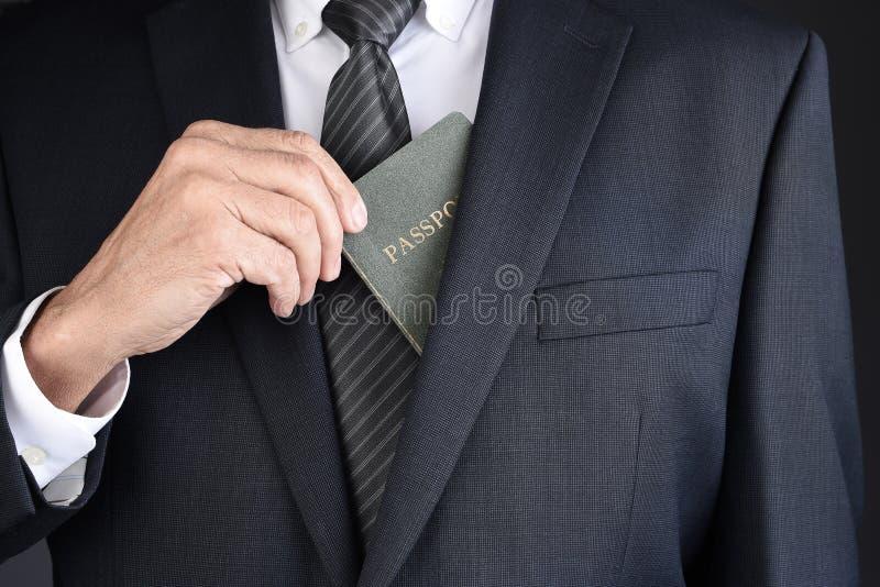 Primer de un hombre de negocios que toma su pasaporte para sus chaquetas del traje dentro del bolsillo del pecho imagen de archivo