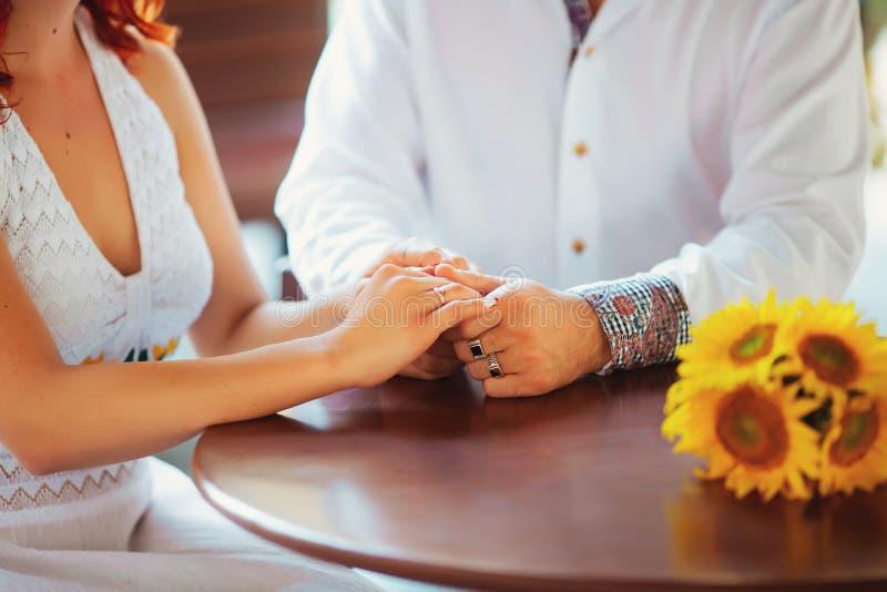 Primer de un hombre que celebra su mano de la esposa en el restaurante foto de archivo libre de regalías