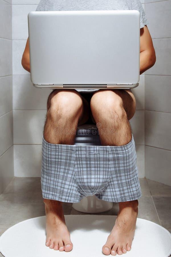 Primer de un hombre que se sienta en el retrete usando el ordenador portátil fotos de archivo libres de regalías