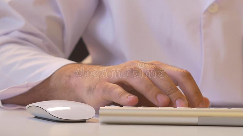 Primer de un hombre que usa el ordenador Su camisa y lazo en fondo foto de archivo
