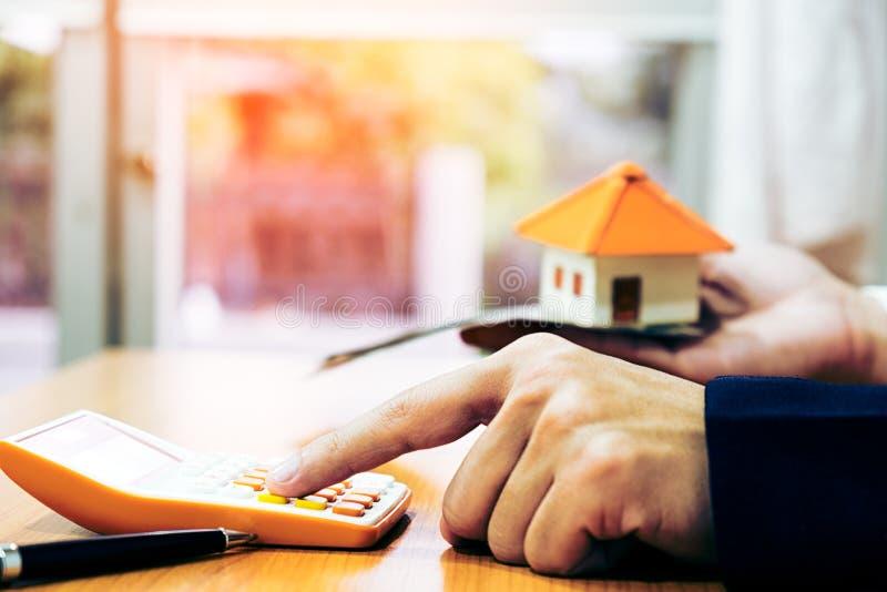 Primer de un modelo In Office de la casa de Using Calculator Besides del hombre de negocios imágenes de archivo libres de regalías
