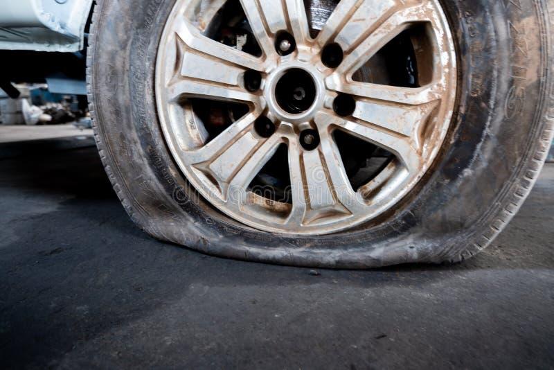 Primer de un neumático desinflado dañado de un coche fotografía de archivo