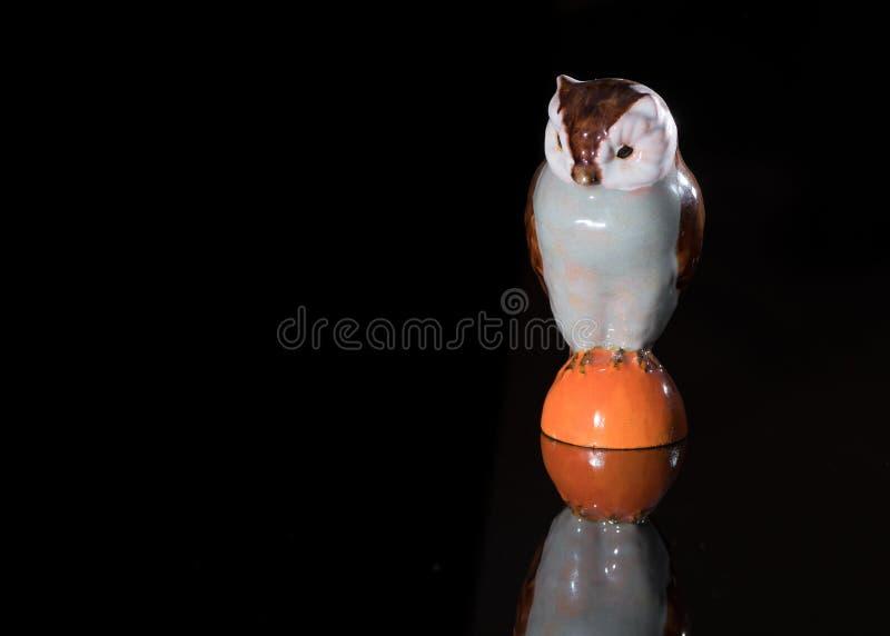 Primer de un pequeño búho de la porcelana que se coloca en un surfac reflexivo fotografía de archivo