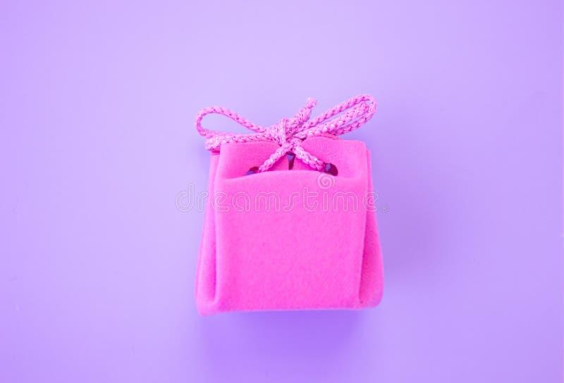 Primer de un peque?o regalo envuelto con la cinta rosada Peque?o rect?ngulo de regalo Profundidad del campo baja Endecha plana, v imagenes de archivo