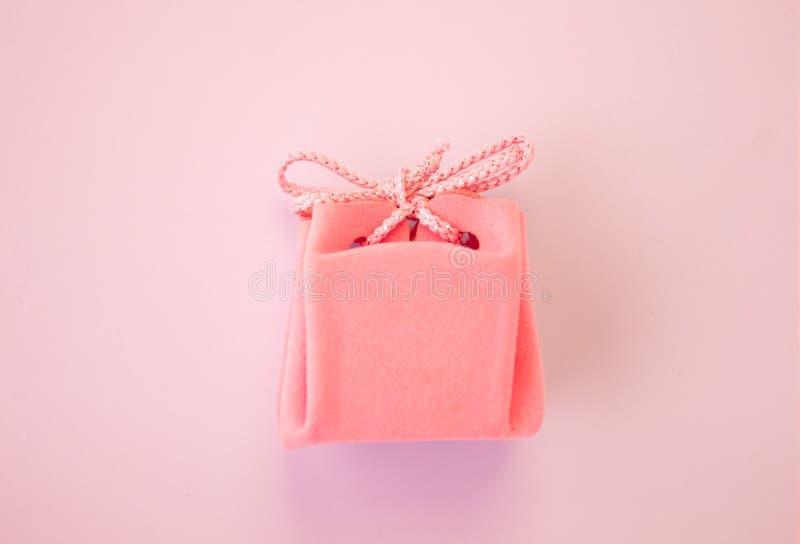 Primer de un peque?o regalo envuelto con la cinta rosada Peque?o rect?ngulo de regalo Profundidad del campo baja Endecha plana, v fotos de archivo
