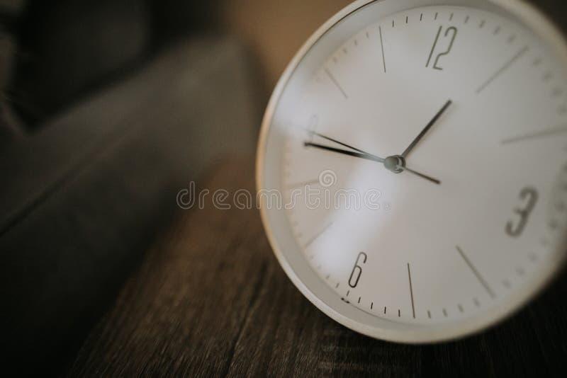 Primer de un reloj blanco en una superficie marrón de madera imagen de archivo