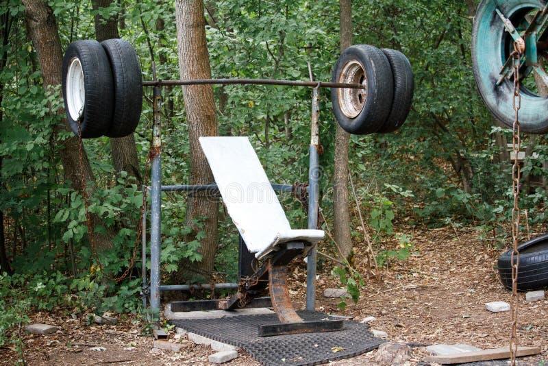 Primer de un simulador hecho en casa áspero de los neumáticos viejos entre árboles gruesos en un parque de la ciudad, concepto sa foto de archivo