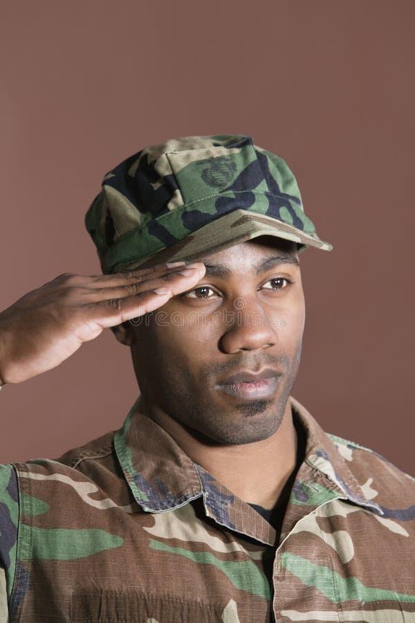 Primer de un soldado joven de los E.E.U.U. Marine Corps del afroamericano que saluda sobre fondo marrón fotos de archivo libres de regalías
