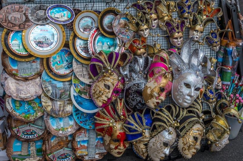 Primer de un soporte de la calle que vende recuerdos como máscaras del carnaval y las placas en Pisa, Italia imagen de archivo libre de regalías