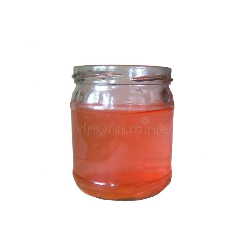 Primer de un tarro de cristal aislado con el líquido Vidrio claro, líquido rosado imagen de archivo libre de regalías