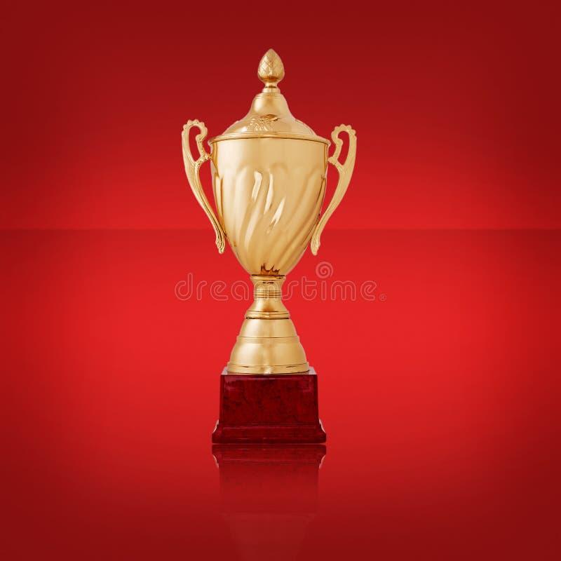 Primer de un trofeo de oro brillante, en rojo imagen de archivo libre de regalías