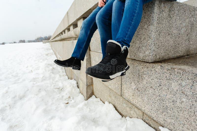 Primer de un viajero feliz y cariñoso del pie de los pares que se sienta en la costa del granito Un par en los zapatos del invier foto de archivo libre de regalías