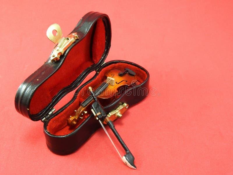Primer de un violín miniatura dentro de su caja negra, en una superficie rosada fotografía de archivo