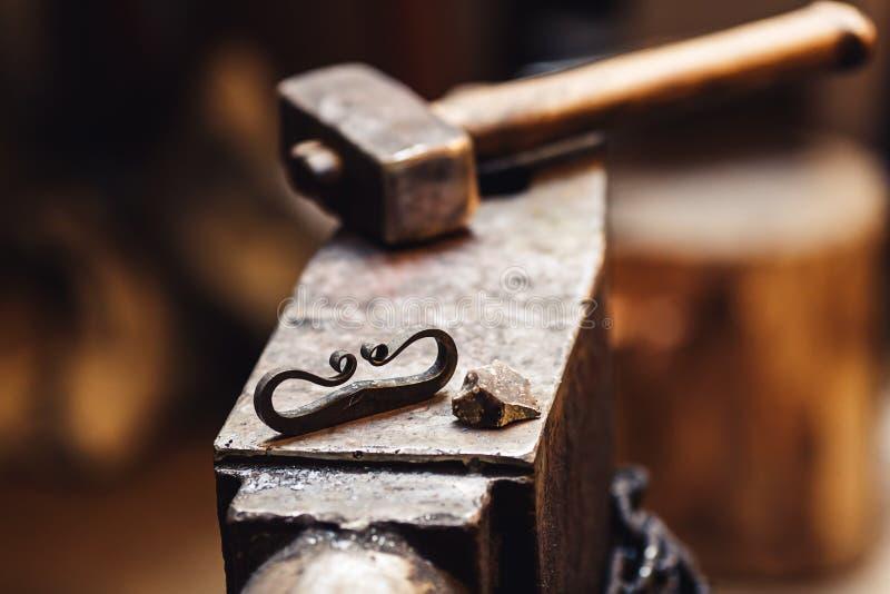 Primer de un yunque del herrero con un martillo, un firesteel y un pedernal fotografía de archivo libre de regalías