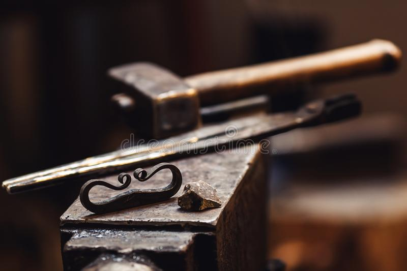 Primer de un yunque del herrero con un martillo, las pinzas, el firesteel y el pedernal foto de archivo
