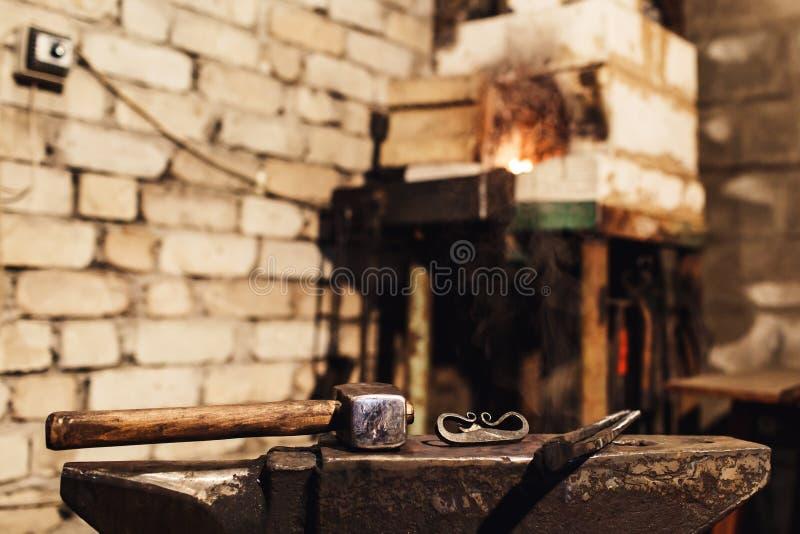 Primer de un yunque del herrero con un martillo, las pinzas y el firesteel imágenes de archivo libres de regalías