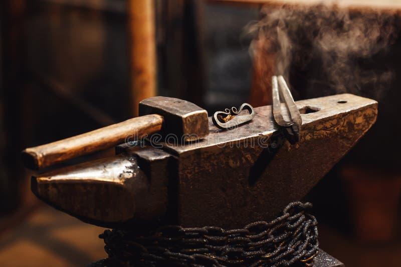 Primer de un yunque del herrero con un martillo, las pinzas y el firesteel imagenes de archivo