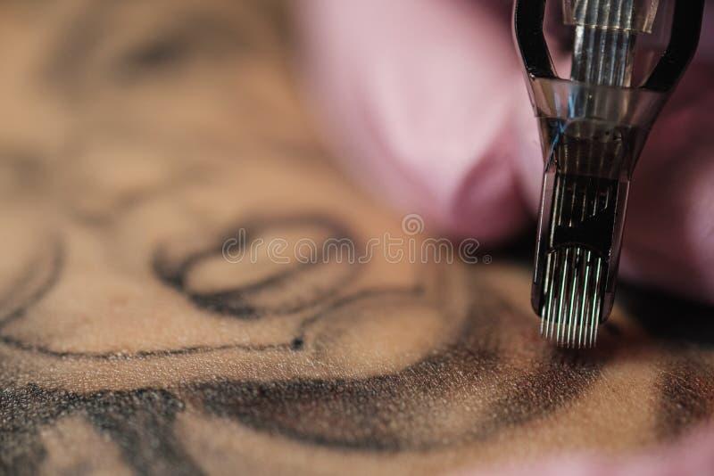 Primer de una aguja del tatuaje El proceso del amo del tatuaje Los guantes protectores de las mujeres del rosa imagen de archivo