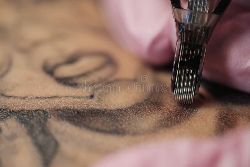 Primer de una aguja del tatuaje El proceso del amo del tatuaje Los guantes protectores de las mujeres del rosa imagenes de archivo