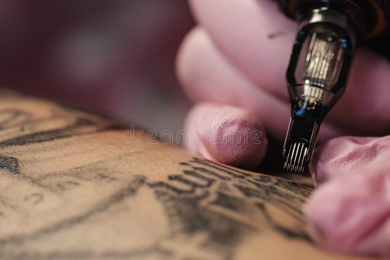 Primer de una aguja del tatuaje El proceso del amo del tatuaje Los guantes protectores de las mujeres del rosa fotografía de archivo