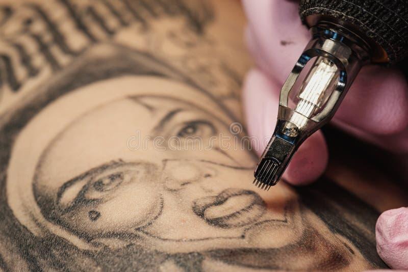 Primer de una aguja del tatuaje El proceso del amo del tatuaje Los guantes protectores de las mujeres del rosa fotos de archivo