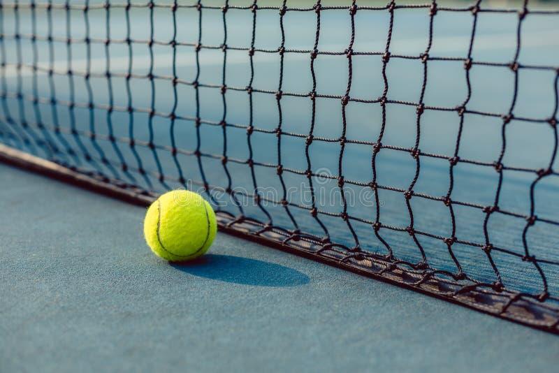 Primer de una bola amarilla fluorescente delante de la red de una pista de tenis foto de archivo libre de regalías