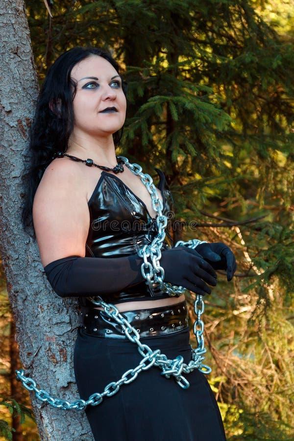 Primer de una bruja de la mujer joven en el negro encadenado a un árbol en un bosque Halloween foto de archivo