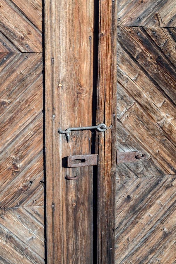 Primer de una cerradura aherrumbrada vieja en una puerta rural rústica con los tablones de madera resistidos naturales decorativo imagenes de archivo