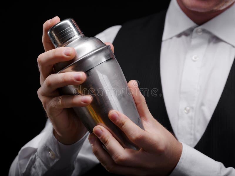 Primer de una coctelera Metal la coctelera de cóctel en manos de un camarero en un fondo negro Concepto del equipo del club noctu imagen de archivo