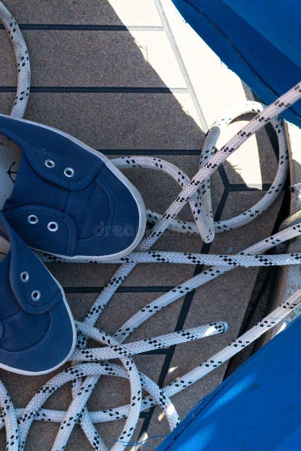 Primer de una cuerda con un extremo anudado atado alrededor de un listón en un embarcadero de madera y los zapatos con las anclas foto de archivo