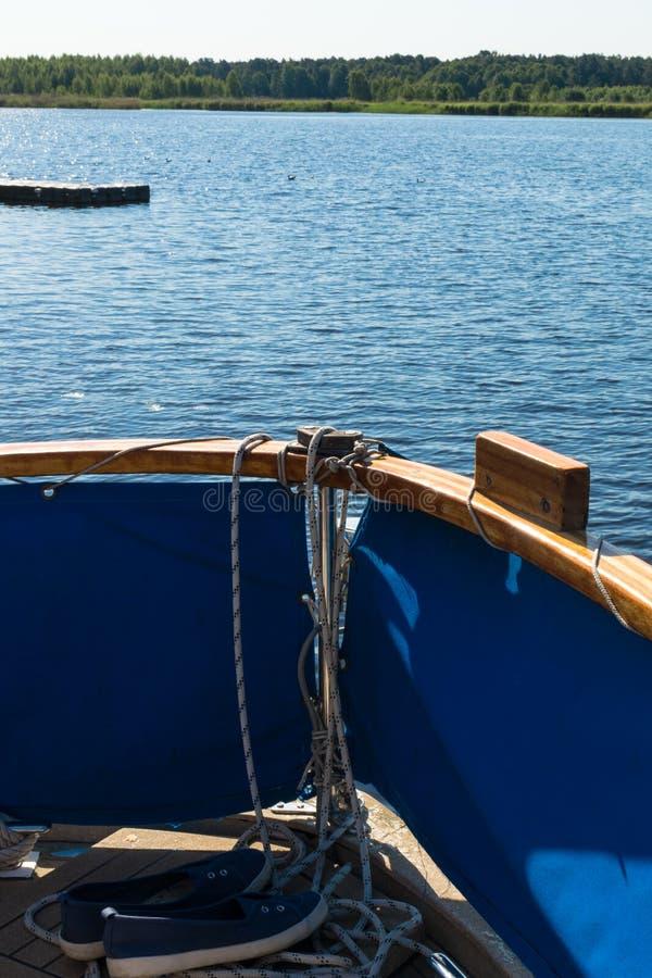 Primer de una cuerda con un extremo anudado atado alrededor de un listón en un embarcadero de madera y los zapatos con las anclas fotos de archivo