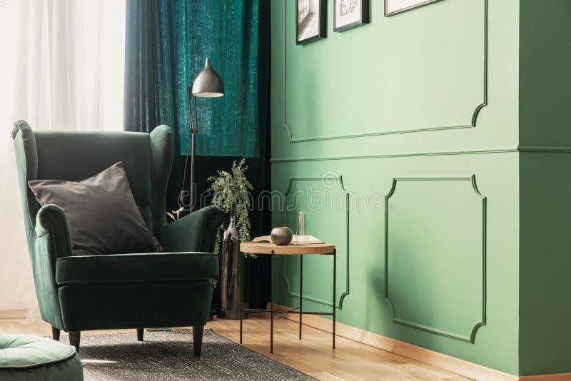 Primer de una esquina de lectura brillante, verde de una sala de estar con una almohada gris en una butaca del terciopelo al lado fotografía de archivo