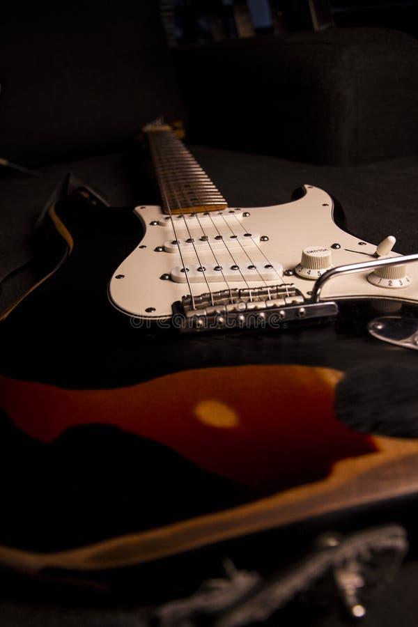 Primer de una guitarra eléctrica resplandor-coloreada cubierta con la pintura negra quitada en ciertos puntos para crear el efect imagen de archivo libre de regalías