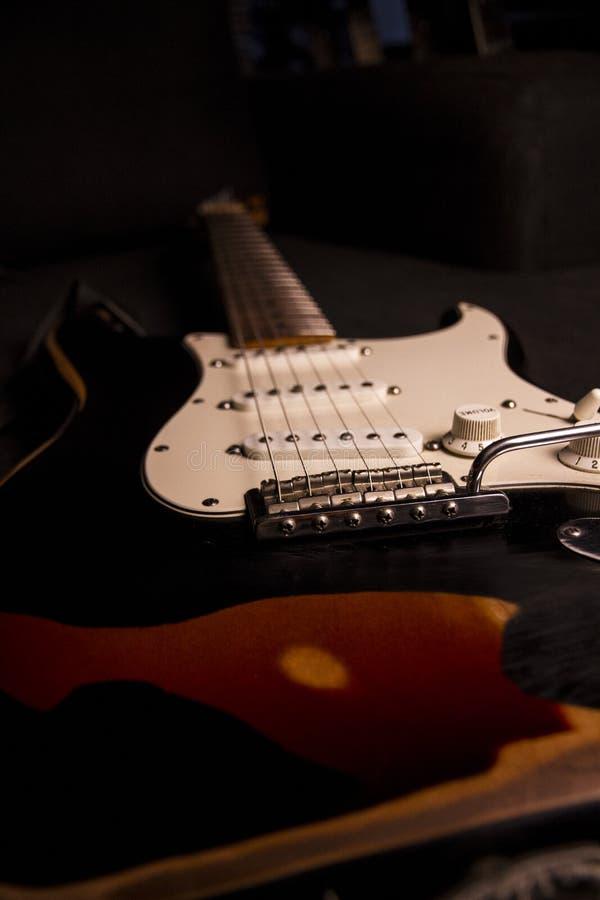 Primer de una guitarra eléctrica resplandor-coloreada cubierta con la pintura negra quitada en ciertos puntos para crear el efect imagenes de archivo