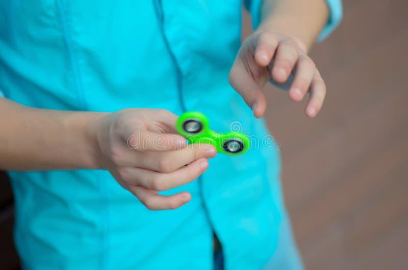 Primer de una mano del ` s del adolescente que juega a un hilandero verde, fotos de archivo libres de regalías