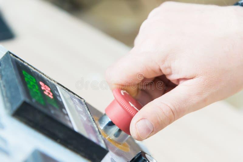 Primer de una mano del ` s del hombre en un botón rojo en el panel de control  Parada de emergencia o comienzo del equipo y de la fotos de archivo