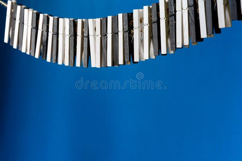 Primer de una mano del ` s de la mujer que juega el piano imaginario hecho de los pernos de ropa en fondo del papel azul fotos de archivo libres de regalías