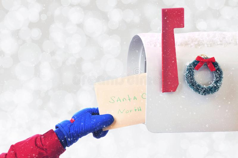 Primer de una mano de los childs que pone una letra a Santa Claus en un mA imagen de archivo