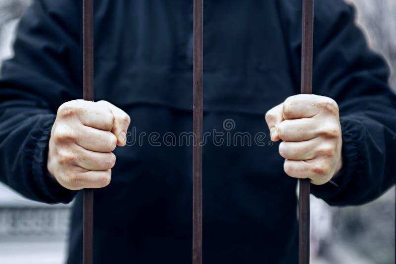 Primer de una mano que sostiene una jaula de acero, concepto del preso Manos del preso en c?rcel Esperanza de estar libre foto de archivo libre de regalías